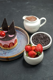 Bolo de queijo delicioso de vista frontal com morango e chocolate em tigelas de prato com chocolate escuro de morangos de chocolate no fundo escuro isolado