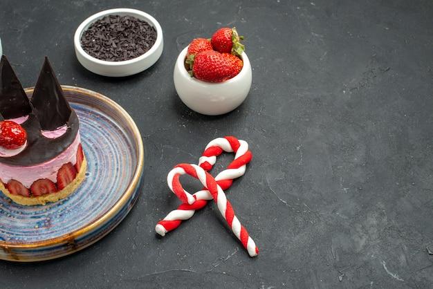 Bolo de queijo delicioso de vista frontal com morango e chocolate em tigelas de prato com morangos e bombons de chocolate de natal em fundo escuro isolado com local de cópia