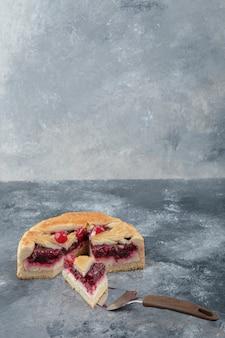 Bolo de queijo fatiado com frutas vermelhas colocadas sobre superfície de mármore.