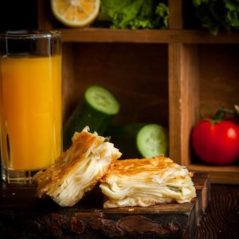 Bolo de queijo folhado com suco de laranja e pepino e tomate e alface na prancha de madeira
