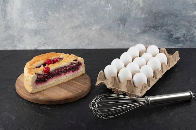 Bolo de queijo saboroso fatiado com frutas vermelhas, bigode e ovos crus na superfície preta.
