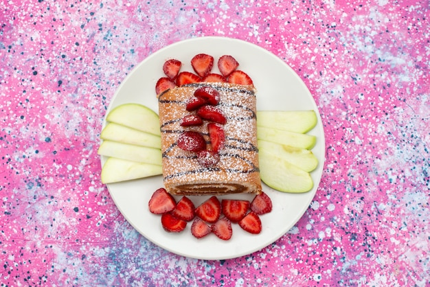 Bolo de rolo com frutas dentro de um prato branco no fundo colorido bolo de biscoito de cor doce
