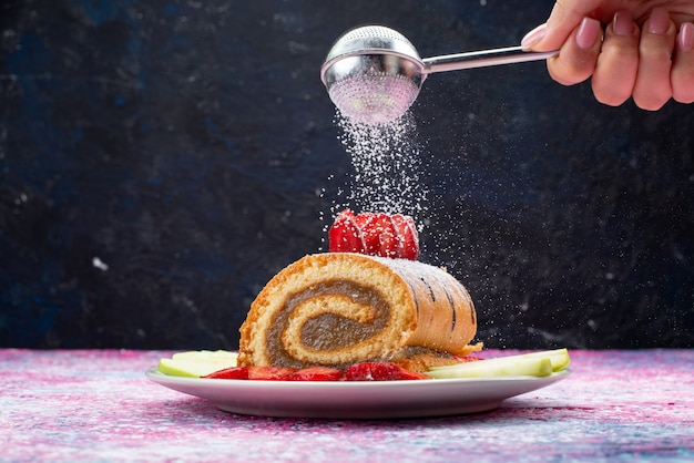 Bolo de rolo com frutas em prato branco de frente