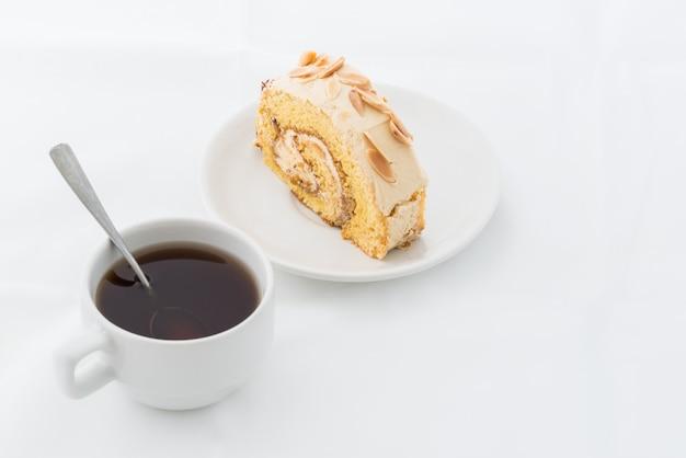 Bolo de rolo de amêndoa no prato branco com bebida quente