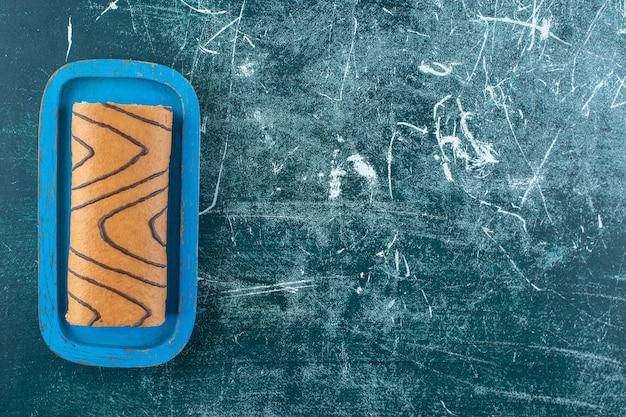 Bolo de rolo saboroso em uma placa preta, sobre o fundo azul. foto de alta qualidade