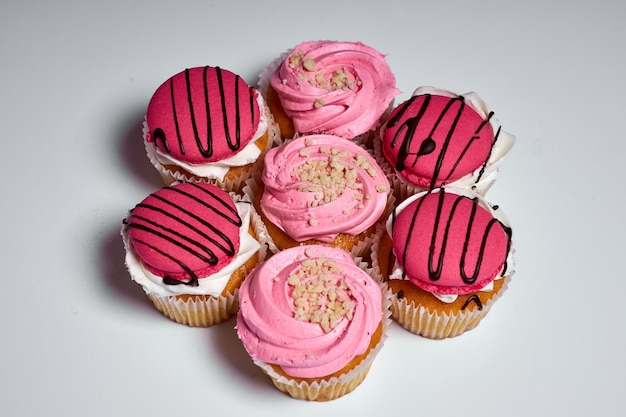 Bolo de sobremesa deliciosos muffins com creme rosa guloseima doce conjunto de bolos em um fundo branco