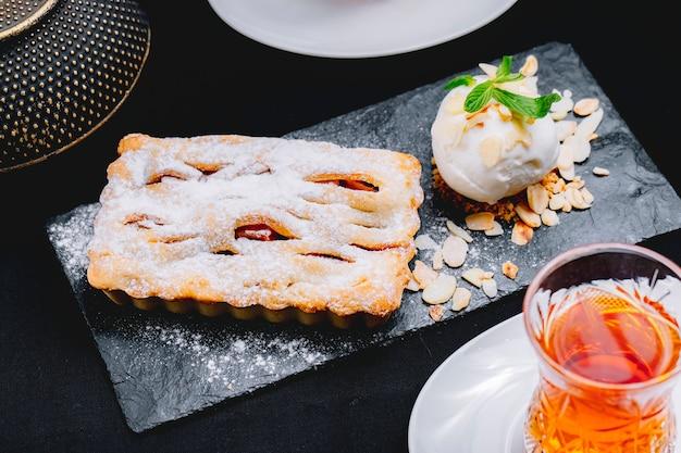 Bolo de sobremesa vista frontal com sorvete e um copo de chá