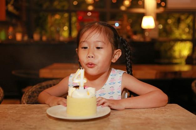 Bolo de sopro do feliz aniversario da menina asiática pequena adorável da criança 4 anos velho.
