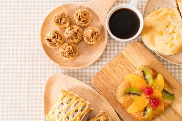 Bolo de toffee, pão com maionese de maionese, taro tartes, frutas misturadas dinamarquesas com geléia e xícara de café