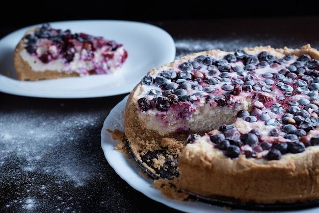 Bolo de torta de frutas vermelhas com groselha de cerejas em uma tigela de vapor fresco um todo e fatias
