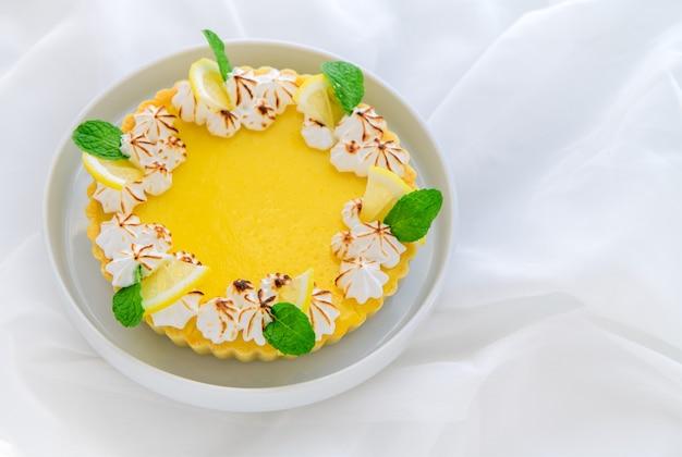 Bolo de torta de limão cítrico em prato branco e fundo de pano branco, conceito de bolo e padaria