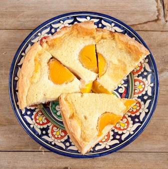 Bolo de torta de pêssego fatiado em prato multicolorido com fundo de madeira