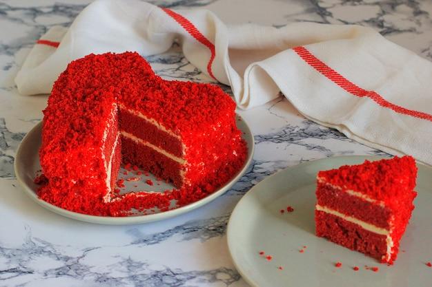 Bolo de veludo vermelho em forma de coração na fatia de mesa de mármore de lado