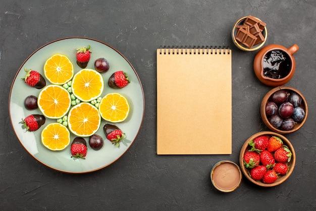 Bolo de visão superior com caderno de creme de morango entre chocolate de morangos em tigelas e prato de morangos de laranja picados e chocolate na superfície escura