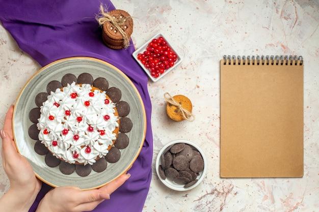 Bolo de vista superior com creme de confeiteiro no prato em bolinhos de xale roxo de mão feminina amarrados com frutas vermelhas e chocolate no caderno tigela na mesa branca