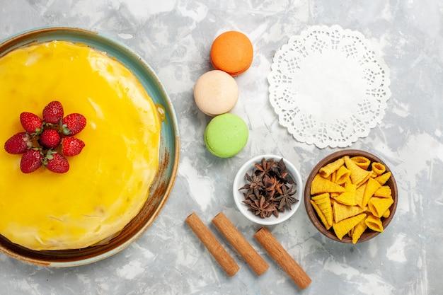 Bolo de xarope amarelo com macarons franceses em fundo branco.
