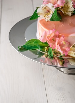 Bolo decorado com flores. bolo de casamento em um carrinho sobre um fundo branco de madeira