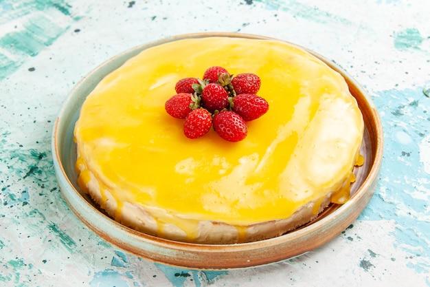 Bolo delicioso com calda amarela e morangos vermelhos na mesa azul de frente