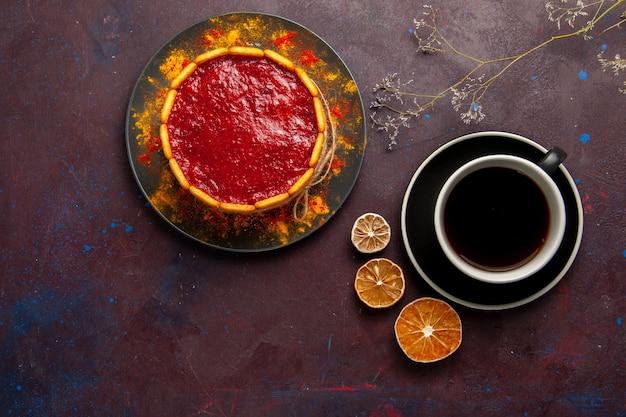 Bolo delicioso com creme vermelho e uma xícara de café no fundo escuro bolo de biscoito torta de sobremesa de açúcar bolo doce