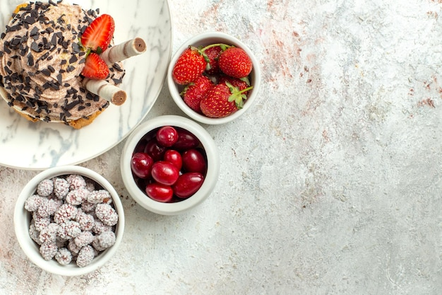 Bolo delicioso cremoso com frutas frescas na superfície branca bolo de chá de aniversário biscoito doce com vista de cima