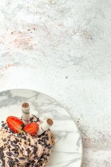 Bolo delicioso cremoso com morangos em uma superfície branca clara com creme de chá e biscoito bolo de aniversário doce