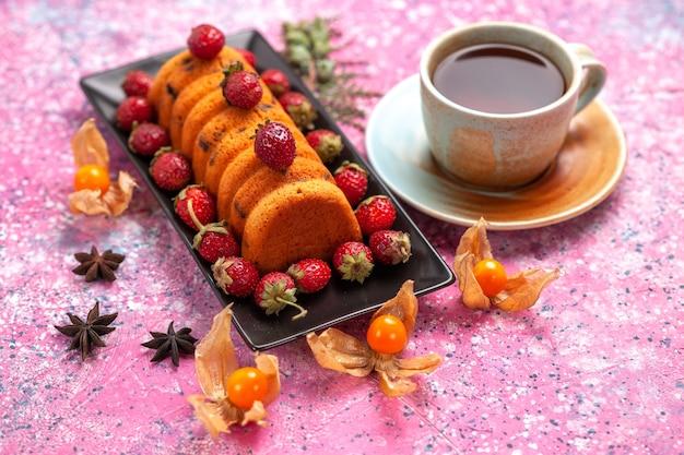 Bolo delicioso de vista frontal dentro de uma fôrma preta com morangos vermelhos frescos e uma xícara de chá na mesa-de-rosa.