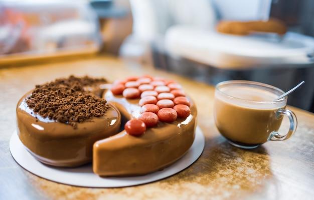 Bolo delicioso e adorável na cozinha de casa em uma mesa de madeira e uma xícara de café perfumado