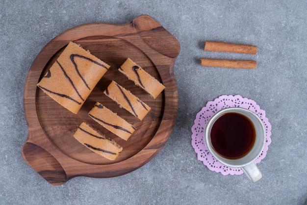 Bolo delicioso em um prato de madeira com uma xícara de chá