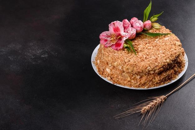 Bolo delicioso fresco napoleon com creme em um fundo escuro. bolo constituído por cordões e creme