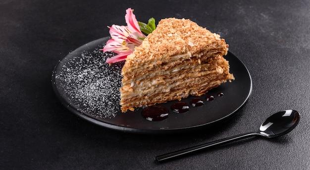 Bolo delicioso fresco napoleon com creme em uma superfície escura. bolo constituído por cordões e creme