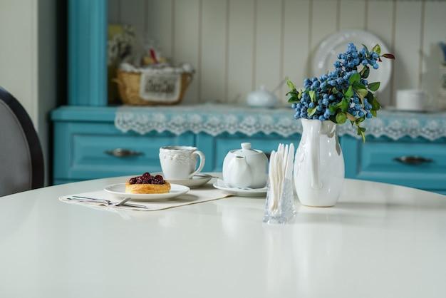 Bolo dinamarquês com cerejas e chá preto em mesa de cafeteria aconchegante