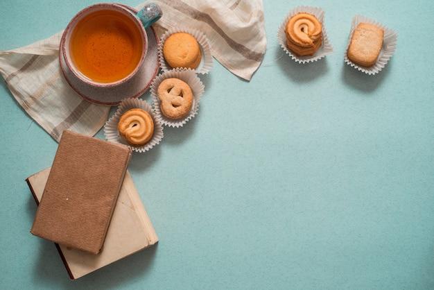 Bolo do bolo do limão com o copo do chá. fundo azul vista do topo.