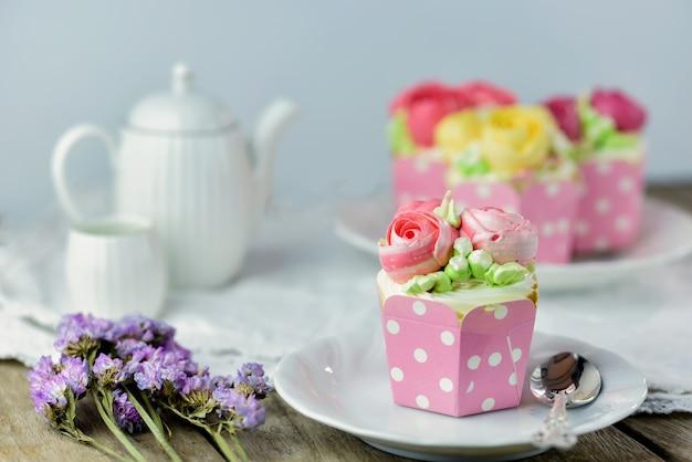 Bolo do copo da baunilha e colher em uma placa com o bolo do copo no fundo para o dia dos valentim, s