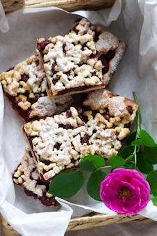 Bolo doce com arenas rosas cereja e streusel sobre um fundo de madeira. estilo rústico.