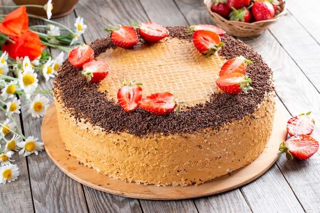 Bolo doce com leite condensado fervido, chocolate e morangos em uma mesa de madeira. vista de perto. fotografia de alimentos de padaria.