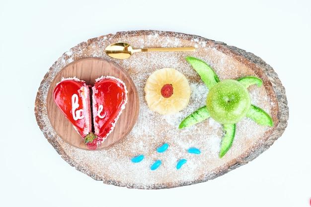 Bolo dos namorados da forma do coração vermelho com frutas.