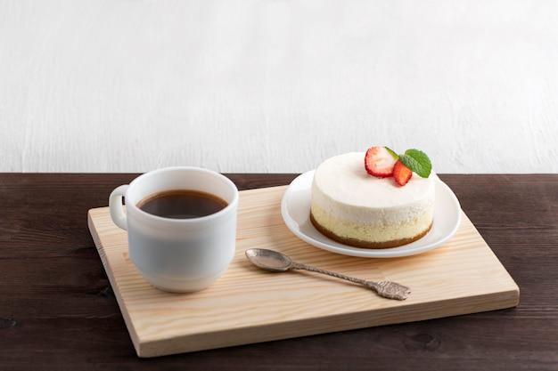 Bolo e café na bandeja de madeira. café da manhã na cama.