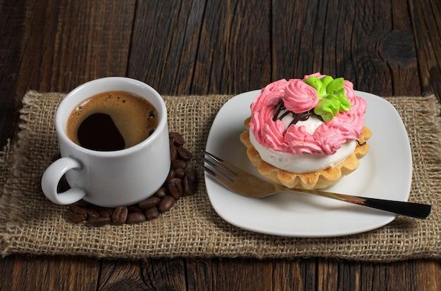 Bolo e café quente na mesa de madeira escura