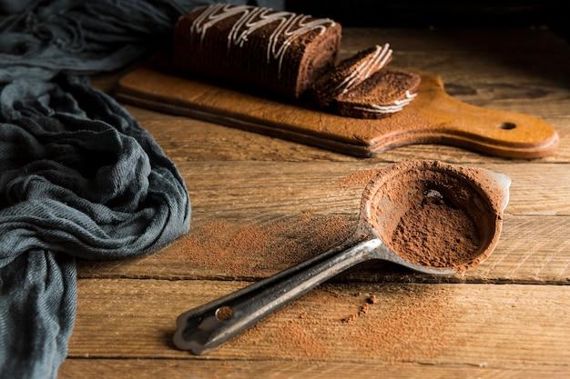 Bolo e filtro de rolo de chocolate fatiado de ângulo alto com cacau em pó