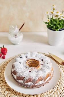 Bolo em anel com frutas e pó em uma mesa branca com superfície branca