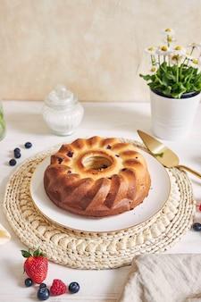 Bolo em anel com frutas em mesa branca com superfície branca
