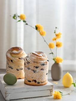 Bolo em camadas de páscoa cruffin com açúcar de confeiteiro e flores amarelas. composição do feriado da páscoa
