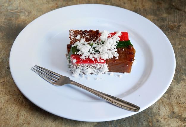 Bolo em camadas e coco ralado no prato com talheres, comida malaia