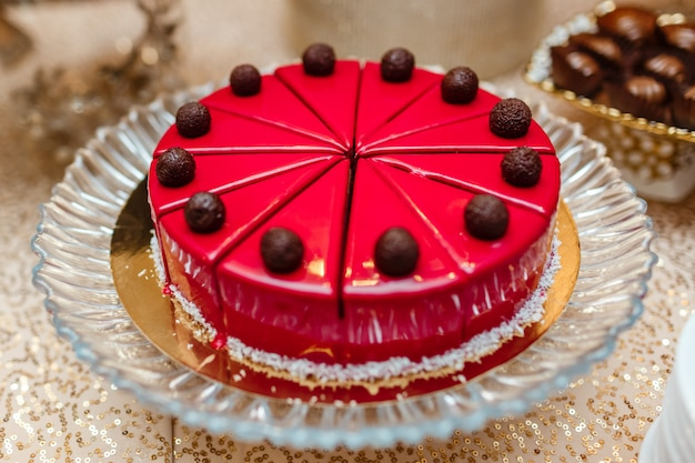Bolo em esmalte vermelho na mesa, corte em pedaços. decorado com bolas de chocolate. barra de chocolate