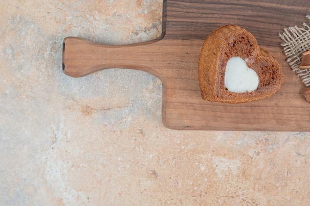 Bolo em forma de coração com creme na placa de madeira.