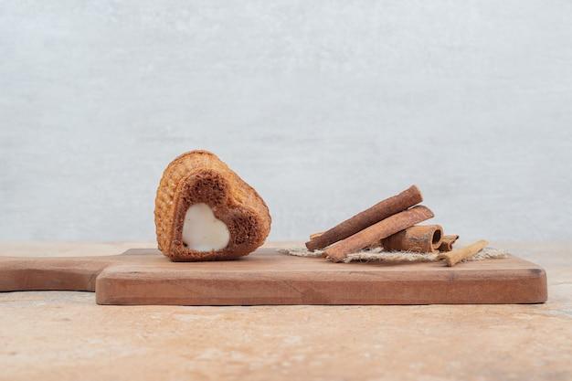 Bolo em forma de coração e palitos de innamon na placa de madeira.