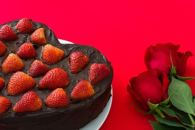 Bolo em forma de coração e rosas vermelhas para dia dos namorados ou dia das mães em fundo vermelho