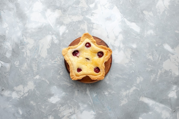 Bolo em forma de estrela com cerejas no interior sobre a mesa cinza bolo em forma de estrela