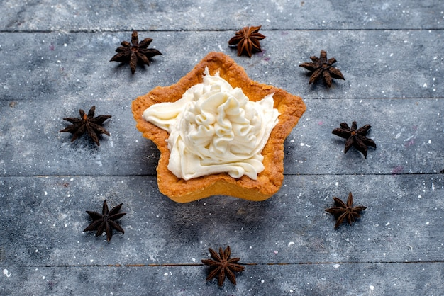 Bolo em forma de estrela com creme na mesa leve, biscoito doce com açúcar e creme de leite