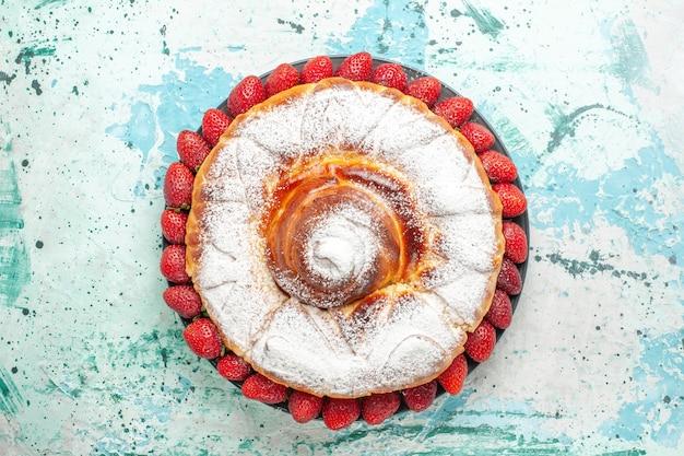 Bolo em pó com açúcar em pó e morangos vermelhos frescos na superfície azul claro